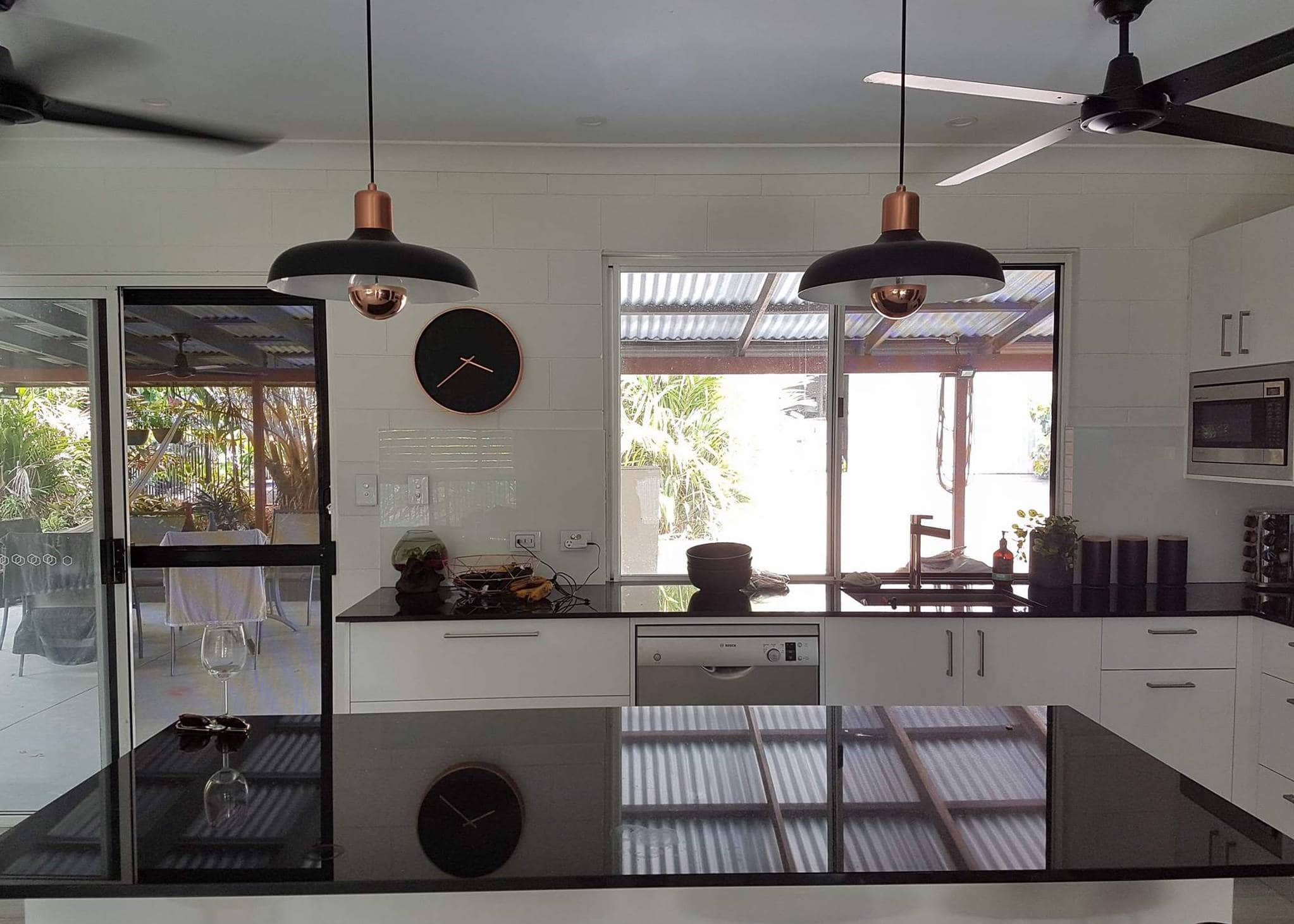 Recently completed electrical renovation with black pendant lights and ceiling fans